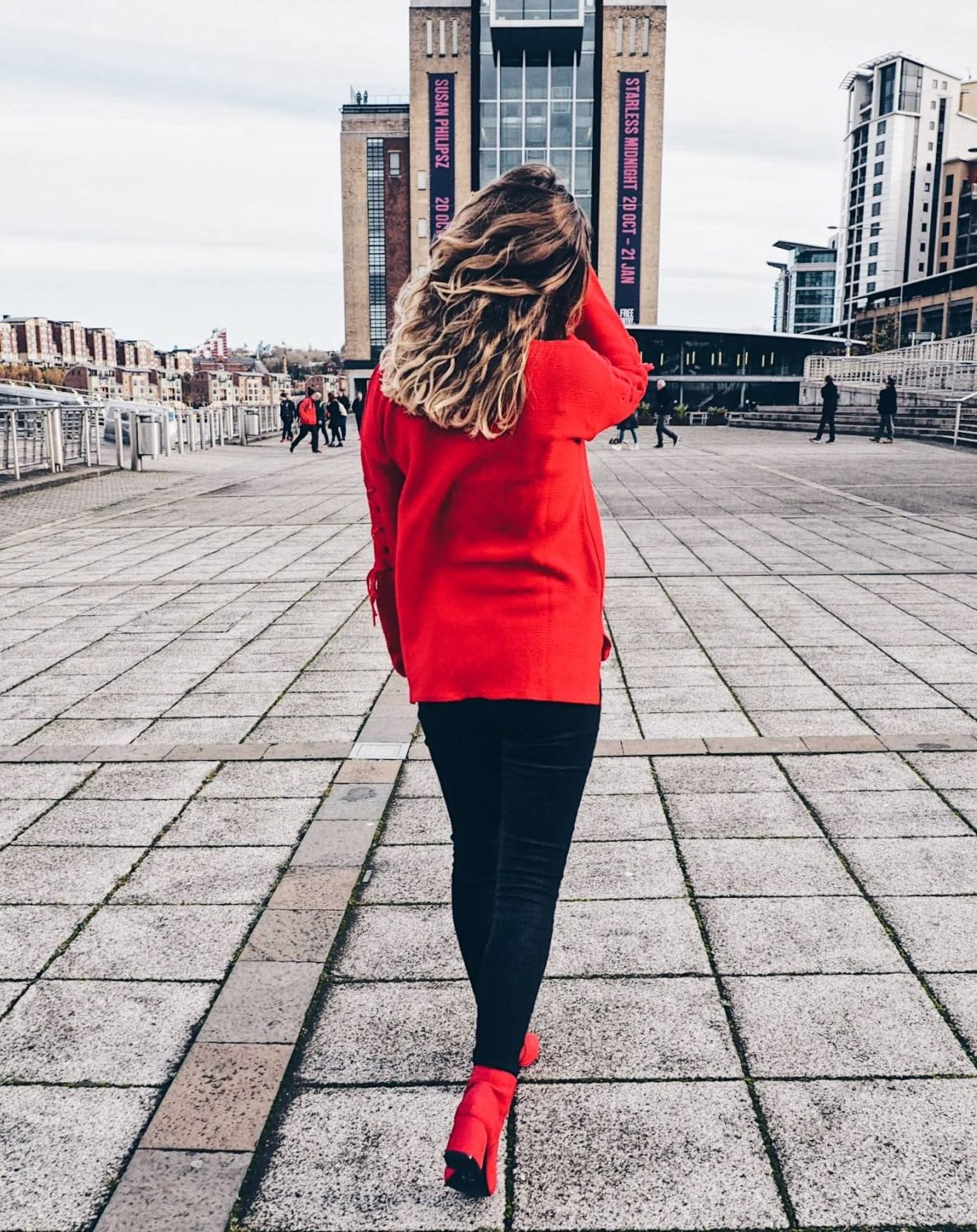 Red jumper, red boots, black jeans